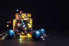 En glödande girland i en glass krus och julpynt på en mörk träbakgrund Nytt år julvykort kopiera avstånd Royaltyfri Foto