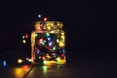 En glödande girland i en glass krus och julpynt på en mörk träbakgrund Nytt år julvykort kopiera avstånd Arkivbild