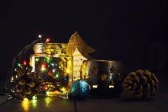 En glödande girland i en glass krus och julpynt på en mörk träbakgrund Nytt år julvykort kopiera avstånd Royaltyfri Fotografi