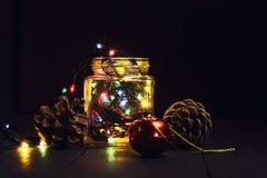 En glödande girland i en glass krus och julpynt på en mörk träbakgrund Nytt år julvykort kopiera avstånd Royaltyfri Bild