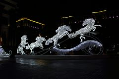 En glödande skulptur för jul i formen av fyra hästar på gatan i aftonen Royaltyfria Bilder