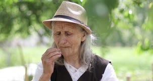 En glad farmor med långt grått hår och en sugrörhatt ser kameran och äter stock video