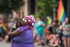 En glade Pride Participant rymmer en hund Royaltyfri Foto