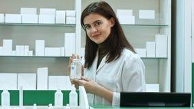 En gladlynt apotekare för ung kvinna med en flaska av droger som står i apotekapoteket som ser kameran royaltyfria bilder
