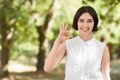 En gladlynt dam på en naturlig bakgrund En nätt brunettflicka som gör en ` det reko `-tecknet Sund flicka som går i en parkera Arkivbild