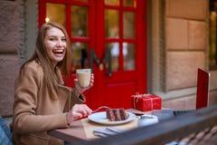 En gladlynt flicka, sitter i ett kafé och äter en efterrätt, dricker något och ler utomhus royaltyfria foton