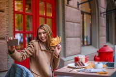 En gladlynt flicka sitter i ett kafé, rymmer ett höstblad och gör selfie på en smartphone royaltyfri fotografi