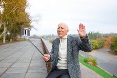 En gladlynt gamal man sitter på par, en vinkande hand och ett innehav en mobiltelefon med en monopod arkivfoto