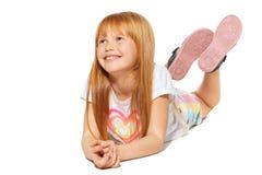 En gladlynt liten flicka med rött hår ligger; isolerat på den vita bakgrunden royaltyfri bild