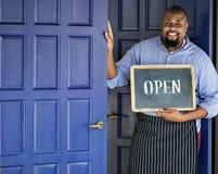 En gladlynt små och medelstora företagägare med det öppna tecknet arkivfoto
