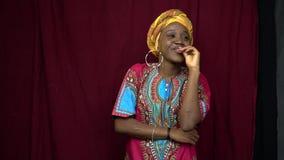 En gladlynt svart kvinna i afrikansk traditionell kläder knäpper fast hennes hand till hennes kanter, hennes händer i ärr lager videofilmer