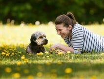 En gladlynt ung kvinna som ligger p? gr?set med hennes husdjur arkivfoton