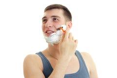 En gladlynt ung man med skum på hans framsida ser upp, och rakningar hans skägg isoleras på en vit bakgrund Royaltyfria Foton