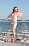 En glamorös dam på en sommarterrass En härlig flicka i en rosa klänning En högväxt dam på en ljus solig bakgrund bakgrundsbegrepp Arkivfoton