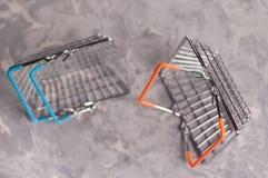 En glansig marknadskorg för tom metall med blåa handtag nära kromkorg med orange gummihandtag arkivbild