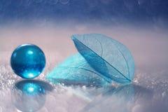 En glass blått klumpa ihop sig och ett genomskinligt bladskelett på en glass tabell med reflexion och en härlig bokeh Royaltyfria Bilder