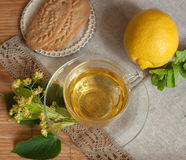 En glass kopp av limefruktblommate, kex och en mogen citron på en träyttersida Fotografering för Bildbyråer