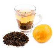 En glass kopp som är full av grönt te En tekopp som isoleras på en vit bakgrund En härlig kopp med naturliga gröna teblad royaltyfri bild