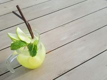 En glass krus av med is det sodavattenlemonad och äpplet är stället på trätabellen Arkivfoto