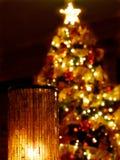 En glass lampa med en stearinljus med ett suddigt tänt julträd i mörkret royaltyfri fotografi