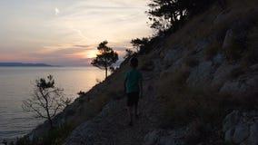 En god man kommer från stranden på ett stenigt berg som förbiser havet och beundrar solnedgången dalmatia croatia lager videofilmer