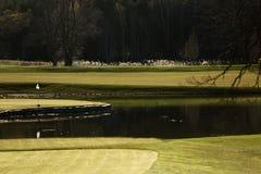 En golfbana med vägar, bunker och damm och med flaggan arkivbilder