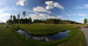 En golfbana med vägar, bunker och damm och med en flod arkivbilder