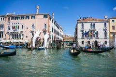En gondoljär i hans gondol i Grand Canal av Venedig framme av gamla slottar VENEDIG, ITALIEN - 14 8 2017 royaltyfria bilder