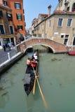 En gondoljär i Venedig navigerar hans gondol till och med en av stads`en s många kanaler royaltyfria bilder