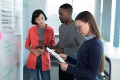 En gráfico de mirada ejecutivo femenino con los colegas en fondo Imagen de archivo libre de regalías