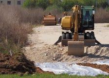 En grävskopa med en rullcompactormaskin på bak att arbeta som bygger en ny väg i bygden arkivbilder