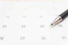 En grå blyertspenna förlägger på en kalender och en punkt på det 23rd datumet Fotografering för Bildbyråer