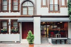 En grå byggnad med en röd dörr, träfönster och en balkong, hotell royaltyfri fotografi