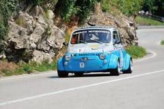 En grå färg och en blått Fiat Abarth 595 tagande särar till det skeppCaino Sant'Eusebio loppet Royaltyfri Fotografi