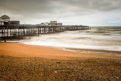 En grå lynnig dag på den Hastings pir och strand Arkivbild
