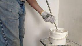 En gråhårig skäggig man blandar vit målarfärg i en hink vid en pinne och häller in i behållaren stock video