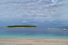 En grön ö i det azura havet Strand, fartyg och molnig himmel royaltyfri foto