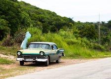 En grön klassisk bil drived i det inlands- Kubaet Arkivbild