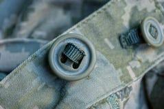 En grön knapp på kamouflagearmékläder royaltyfri bild