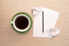 En grön kopp kaffe på tabellen och tömmer arket, blyertspennan, skrynkliga rester Royaltyfri Bild
