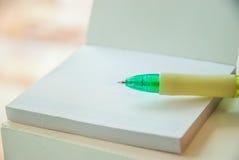En grön penna är pålagt vitt tomt papper Royaltyfria Bilder