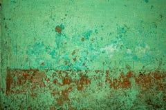 En grön röd gammal betongvägg med djupa skrapor och skada Textur för grov yttersida målarfärg- och smutsfläckar arkivfoton