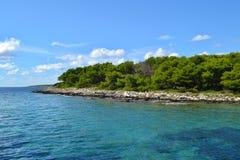 En grön stenig ö i det azura havet blå sky arkivfoto