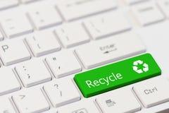 En grön tangent med återanvänder symbolssymbol på det vita bärbar datortangentbordet Arkivfoton
