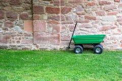 En grön trädgårds- handkärra, skottkärra på fältet för grönt gräs Royaltyfri Fotografi