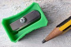 En grön vässare och en blyertspenna på en vit tabell Arkivbilder
