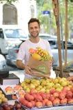 En grönsakshandlare som säljer organiska frukter. Arkivfoton