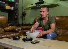 En grabb äter pophavre framme av TV:N arkivfoton