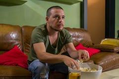 En grabb äter pophavre framme av TV:N arkivfoto