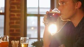 En grabb, i att dricka öl från exponeringsglaset stock video